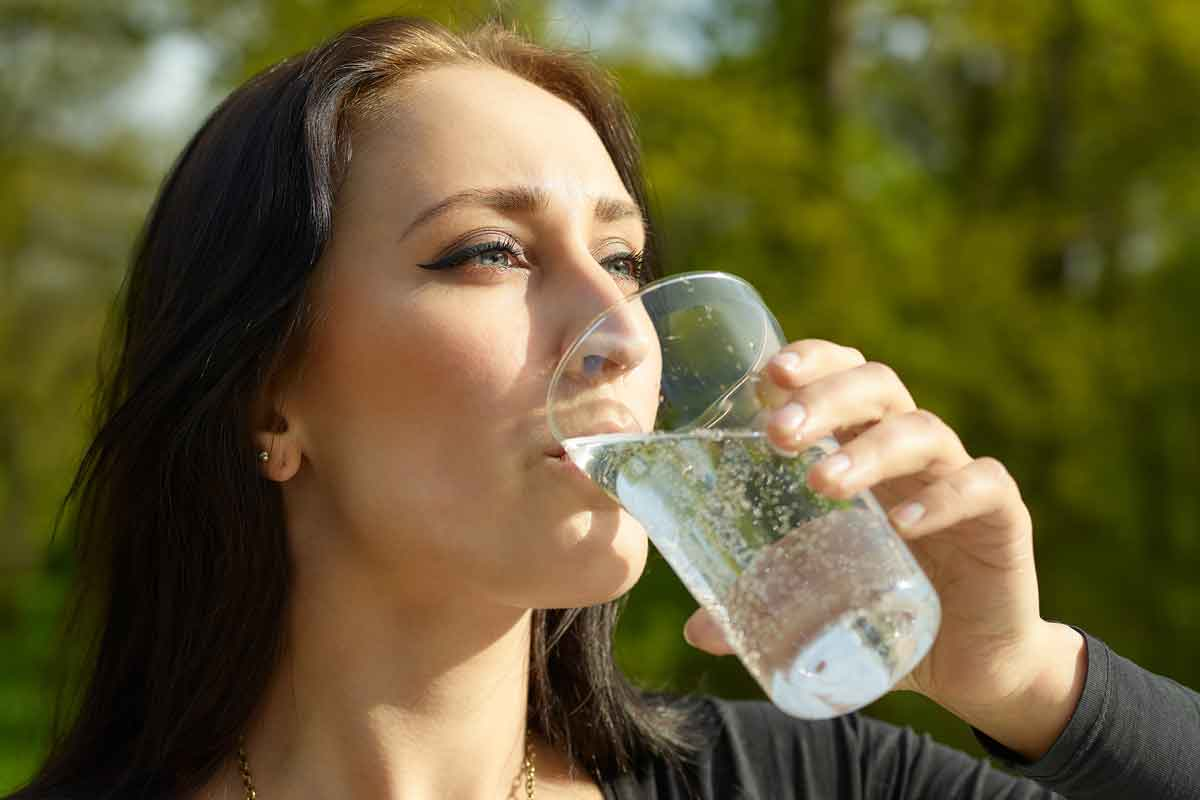 woman drinking sparkling water outside
