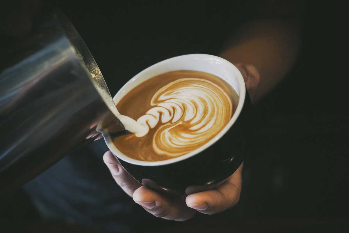 barista pouring the perfect cup of coffee using the creamer to make art