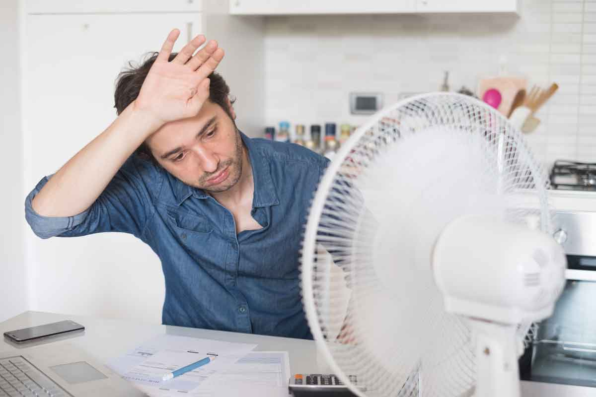 man using a fan to stay cool in the summer