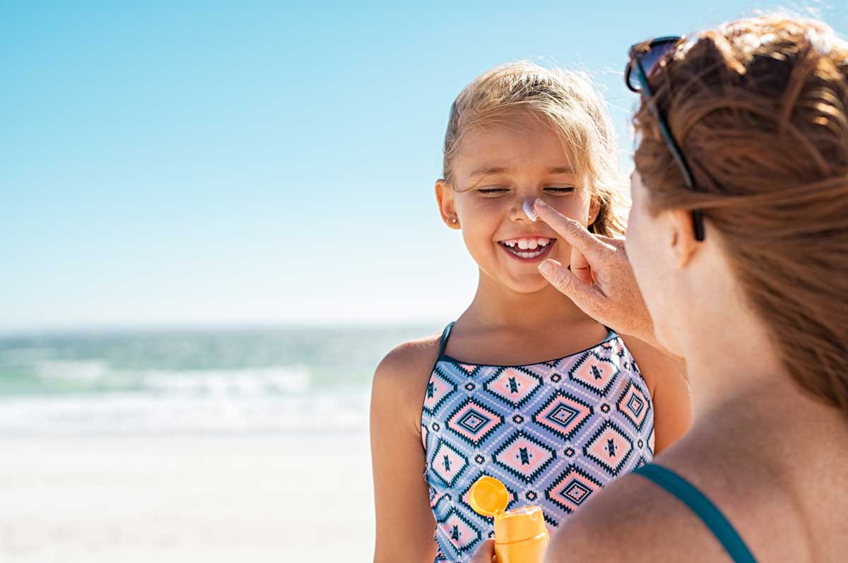 mom putting sunscreen on her daughter at the beach