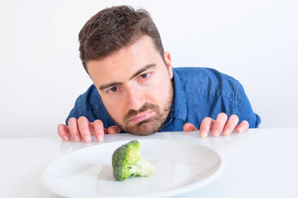 guy staring at vegetable on table